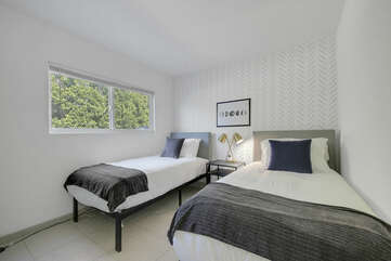 Bedroom 4 is located across from Bedroom 3 and features two Twin-sized Beds, a television.