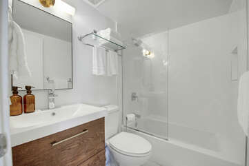 The hallway bathroom is located just off the living area and features a bathtub and shower combo and an extra-wide vanity sink.