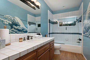 The downstairs full bathroom has a hand painted mural on the wall.