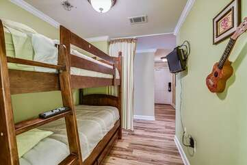 Bunk beds with mounted TV on the wall and privacy curtain