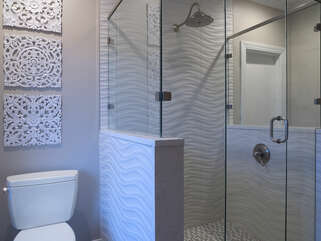 Toilet abuts a large walk in shower.
