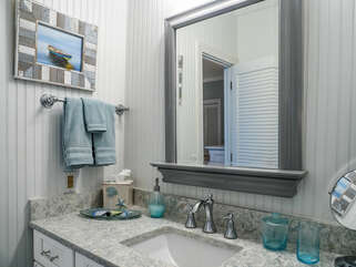 Jack and Jill bathroom is decorated with hues of blue and has a tub.
