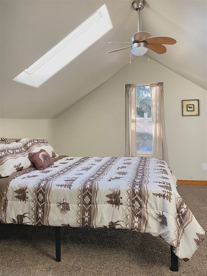 Open concept queen bed with skylight