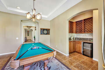 The game room features a wet bar area, wine refrigerator and double french doors to the side yard with a koi pond.