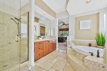 Private, en suite bathroom features a soaking tub, tile shower, and his and hers vanity sinks.