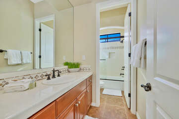 The hallway bathroom is located next to the laundry room and features a shower and tub combo and a vanity sink.