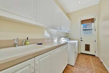 Fully equipped laundry room with washer, dryer, ironing board, iron, and laundry pods.