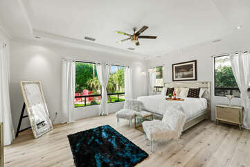 Master Suite 1 is located next to the living room and features a Cal King-sized Bed, 60-inch Samsung Smart television, with access to the back patio and a private, en suite bathroom.