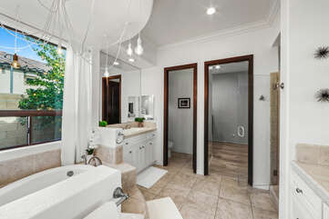 The private, en suite bathroom features a soaking tub, tile shower, and his and hers vanity sinks.