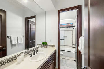 The hallway bathroom is located next to the laundry room and features a bathtub and shower combo with a vanity sink.