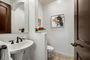 The hallway powder room is located next to the garage and features a pedestal sink.