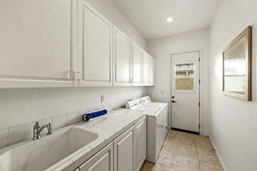 A fully equipped laundry room with washer, dryer, ironing board, iron, and laundry pods.