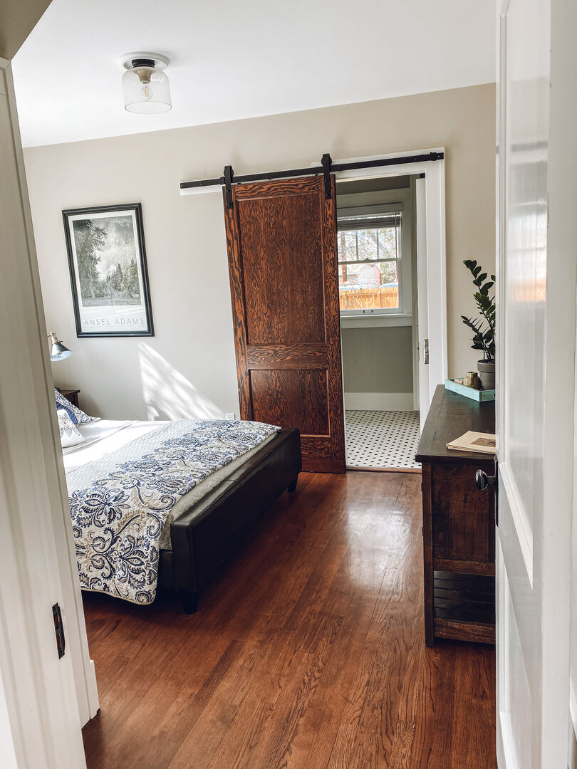 Main level bedroom with queen bed and attached bath