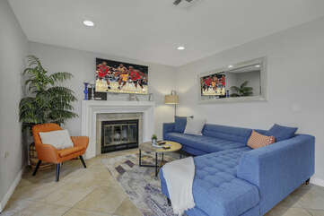 There is plenty of room in the living room to lounge in front of a 60-inch LG Smart television and decorative fireplace.