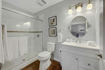 Private, en suite bathroom features a tile shower and a vanity sink.