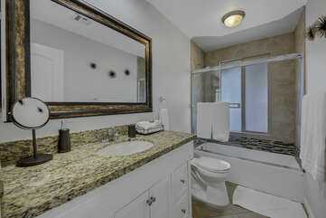 The hallway bathroom is located on the right as you enter the hallway and features a bathtub and shower combo plus a vanity sink.