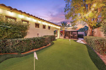 The putting green is located on the side of the home with a beautiful view of the desert landscape.