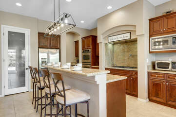 The fully-equipped kitchen features a wine-fridge and stunning stainless steel appliances.