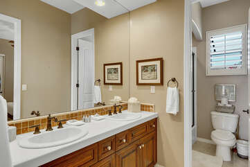 The shared and adjoining, jack and jill bathroom features a shower and tub combo and two vanity sinks.
