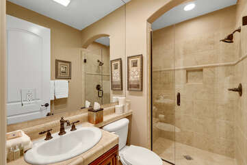 The hallway bathroom is located across from Bedroom 5 and features a tile shower and a vanity sink.