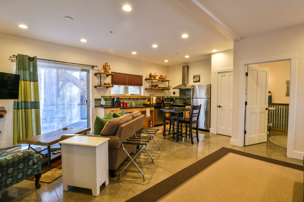 Kitchen with Dining Set, Refrigerator, Sofa, Coffee Table, and TV.