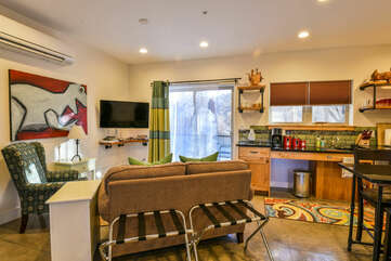 Arm Chair, Sofa, TV Next to the Kitchen, and the Sliding Door to the Patio.
