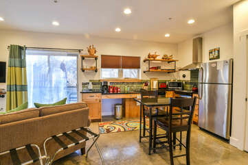 Dining Set in the Kitchen, Refrigerator, Sofa, and the Sliding Door to the Patio.