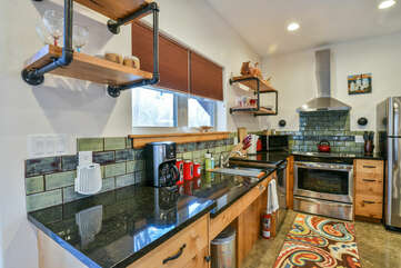Stove, Range Hood, Refrigerator, and Coffee Maker in the Kitchen.