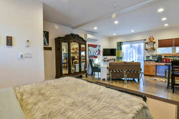 Large Bed, Wardrobe Armoire, Sofas, TV, AC, and Sliding Door to the Patio.
