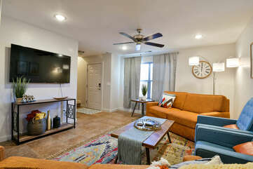 Living Room with TV, Ceiling Fan, Coffee Table, Sofa, and Arm Chairs.