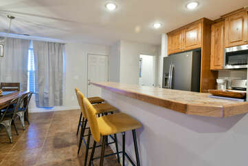 Kitchen with Bar, Stools, Refrigerator, Dining Table and Chairs.