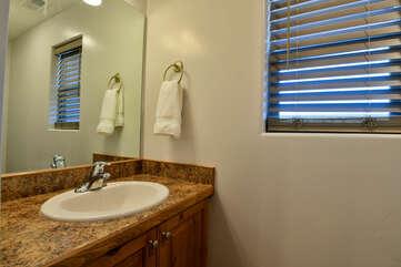 Single Vanity Sink, Mirror, and Window.