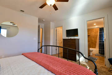 Large Bed, Drawer Chest, TV, Ceiling Fan, and Open Door to the Bathroom.