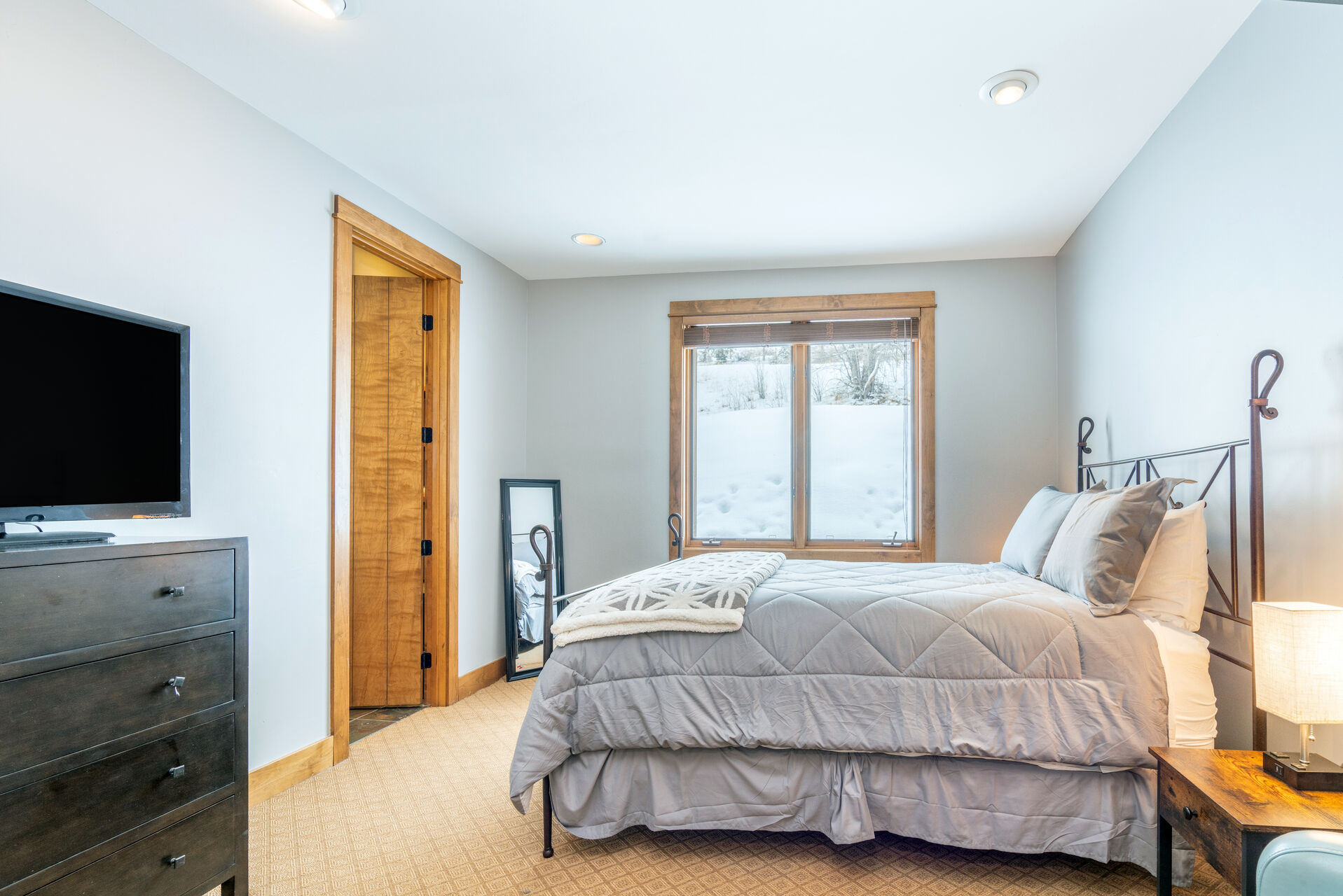 Bedroom with large bed with grey bedspread