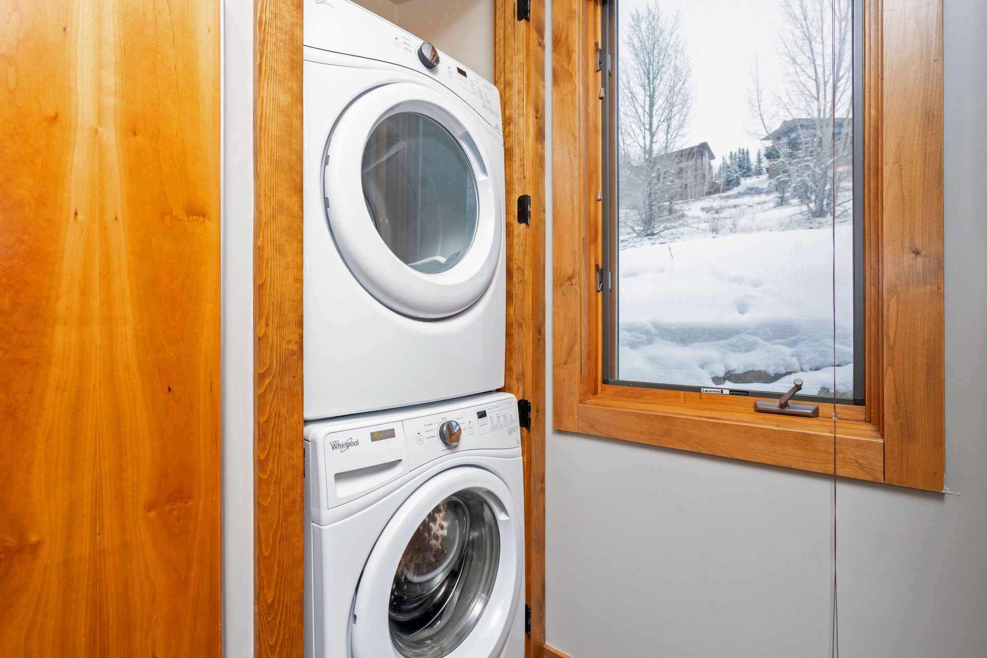 Full-sized stacked washer and dryer next to window with snow view