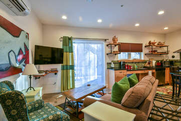 Sofas, Coffee Table, TV, Sliding Door, and the Kitchen.
