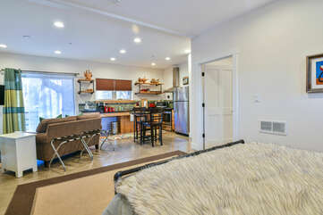 Sofa, Kitchen with Dining Set, Refrigerator, and Sliding Door to the Patio.