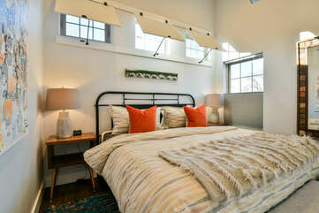 Bedroom with Large Bed, Nightstands, Table Lamps, and Mirror.