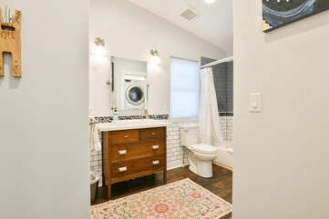 Single Vanity Sink, Mirror, Toilet, and Shower-Tub Combo.