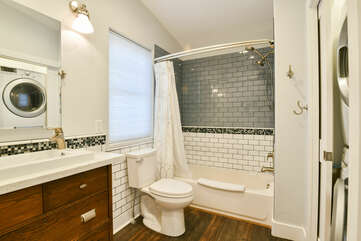Single Vanity Sink, Lamps, Mirror, Toilet, and Shower-Tub Combo.