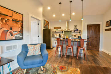 Arm Chair, Kitchen with Island, Stools, Refrigerator, and the Front Door.