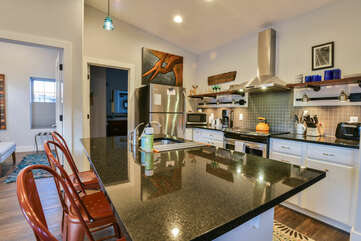 Kitchen with Island, Stools, Refrigerator, Microwave, and the Coffee Maker.