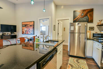 Kitchen Island with Stools, Refrigerator, Microwave, TV, and Sofa.