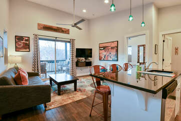 Kitchen Island, Refrigerator, TV, Sofa, Ceiling Fan, and Sliding Door to the Balcony.