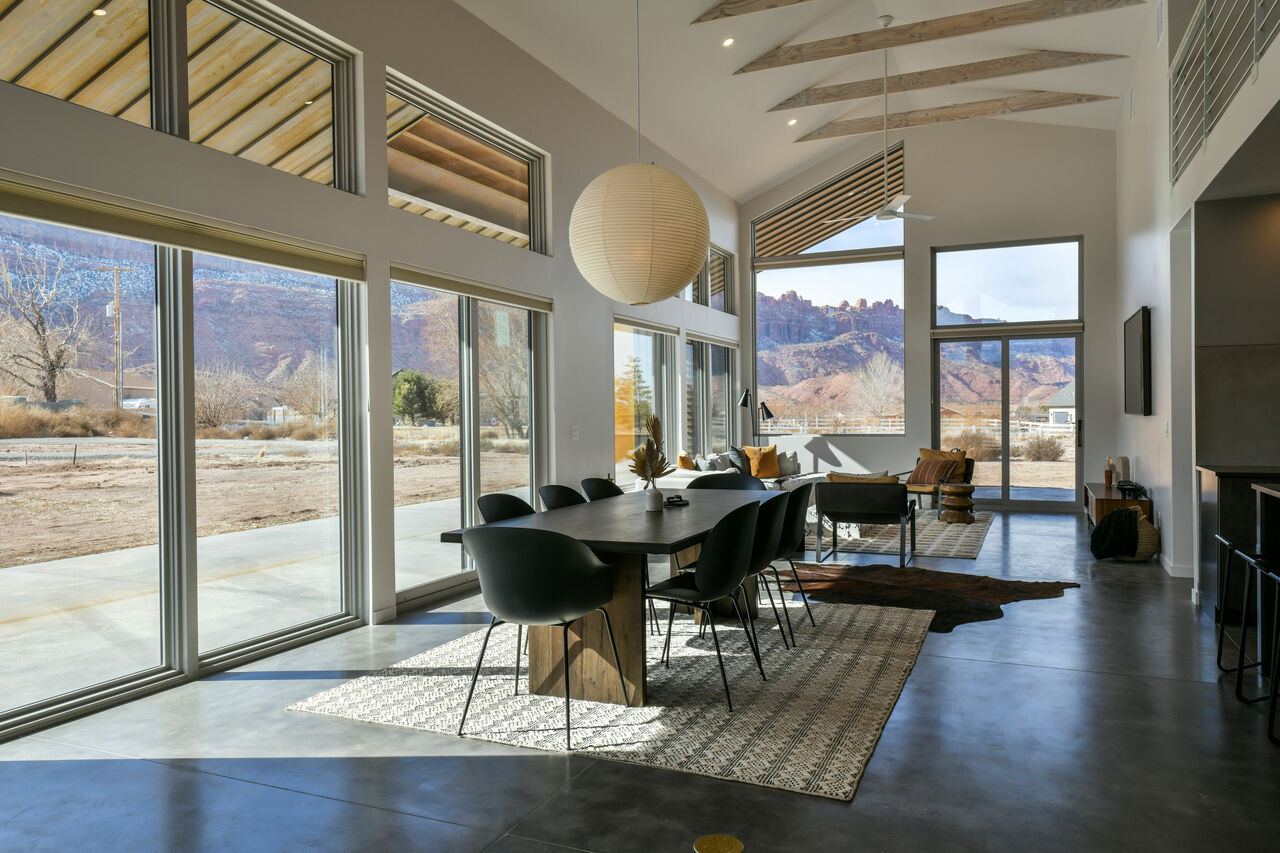 Dining Set, Pendant Lamp, Sofas, TV, and Windows with Mountain Views.
