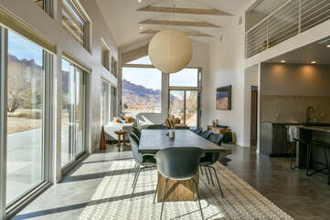 Kitchen Island, Stools, Dining Set, Sofas, TV, and Windows with Mountain Views.