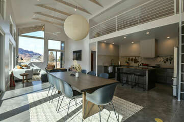 Kitchen with Island, Stools, Dining Set, Sofas, TV, and Windows with Mountain Views.