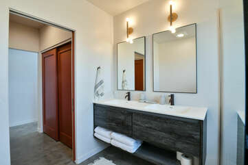 Double Vanity Sink, Mirrors, Wall Lamps, and Sliding Closet Doors.