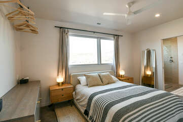 Large Bed, Nightstands, Mirror, Ceiling Fan, Dresser, and Clothes Bar with Hangers.