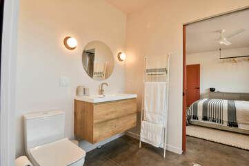 Single Bathroom Vanity Set, Toilet, Mirror, Lamps, and the Open Door to the Bedroom.
